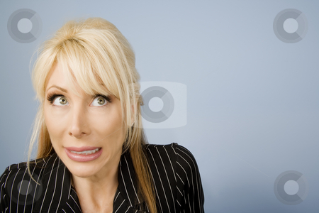 Apprehensive woman stock photo, Close Up of an Apprehensive blonde businesswoman in front of a blue background by Scott Griessel
