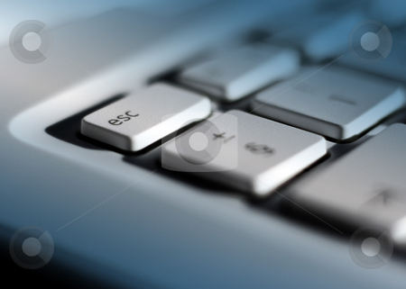 Escaping the office stock photo, Close-up of laptop keyboard with focus on escape key. Blue lighting effect added with clear patch on escape key. by Ronald Hudson