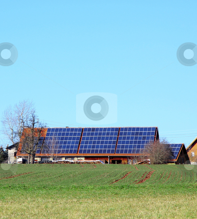 Solar panels stock photo, A Photograph of a house with solar panels by Markus Gann