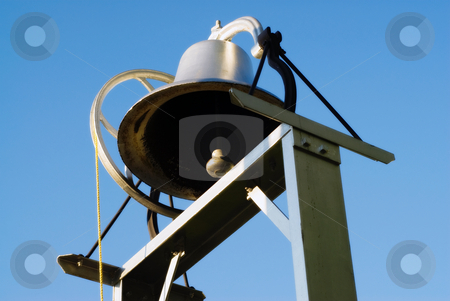 Iron Bell stock photo, Low angle view of a metal school bell, shot against a blue sky by Richard Nelson