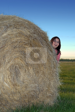 Girl Hiding stock photo, A young girl playing hide and seek behind a hay bale by Richard Nelson