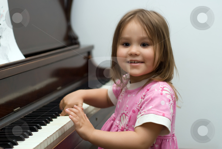 Girl Playing Piano stock photo, Young girl smiling and playing the piano by Richard Nelson
