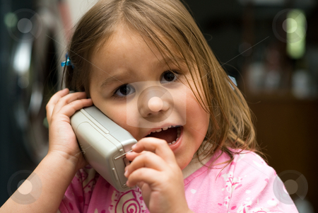 Young Girl On The Phone stock photo, Little girl talking on the phone inside the house by Richard Nelson