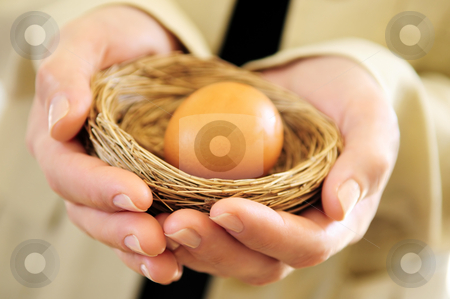 Hands holding nest with an egg stock photo, Hands of a woman holding a nest with an egg by Elena Elisseeva