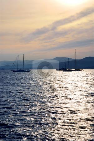 Anchored sailboats stock photo, Anchored sailboats at sunset at Mediterranean coast by Elena Elisseeva