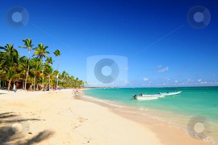 Sandy beach on Caribbean resort  stock photo, Sandy beach on Caribbean resort and fishing boats at sea by Elena Elisseeva