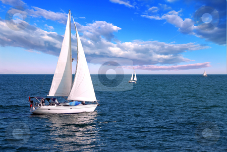 Sailboats at sea stock photo, Sailboat sailing in the morning with blue cloudy sky by Elena Elisseeva