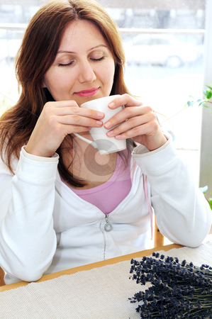 Mature woman relaxing stock photo, Mature woman relaxing at home holding a cup by Elena Elisseeva