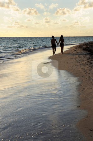 Couple walking on a beach stock photo, Couple taking a walk on a sandy beach of tropical resort by Elena Elisseeva