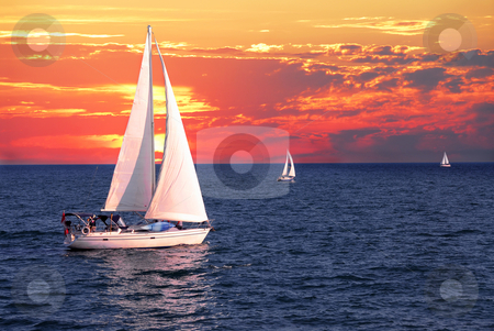 Sailboats at sunset stock photo, Sailboat sailing on a calm evening with dramatic sunset by Elena Elisseeva