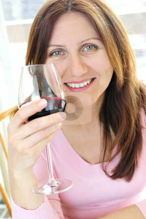 Mature woman with a glass of red wine stock photo, Smiling mature woman holding a glass of red wine by Elena Elisseeva