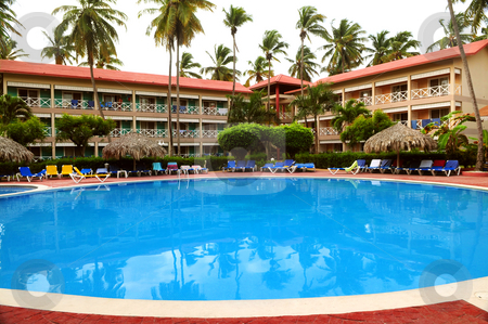 Swimming pool stock photo, Swimming pool and accommodation at tropical resort by Elena Elisseeva