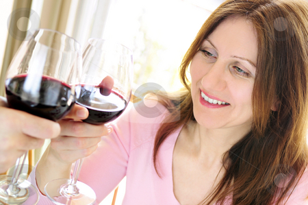 Mature woman toasting with red wine stock photo, Mature woman toasting with a glass of red wine by Elena Elisseeva