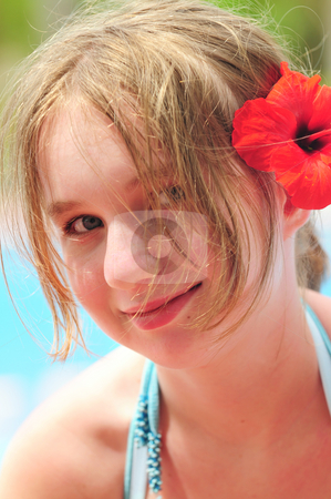 Portrait of a girl with red flower stock photo, Portrait of a young girl on tropical beach with red flower by Elena Elisseeva