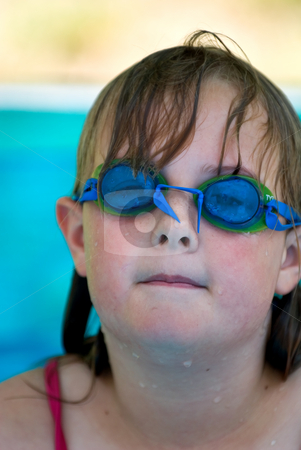Girl with blue goggles stock photo, A young girl with swimming goggles in an inflatable pool by Vince Clements
