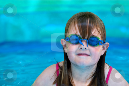 Girl in pool stock photo, A young girl with swimming goggles in an inflatable pool with space on left for type by Vince Clements