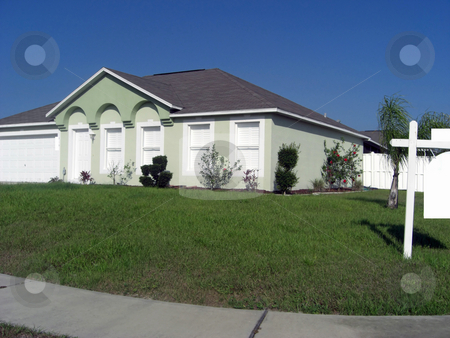 Housing market stock photo, A single family home with an angled roof, a white picket fence, a landscape  and on a corner lot is on the market for sale. by Rebecca Mosoetsa