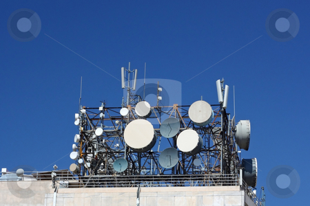 Cluster of Telecommunication Antennas stock photo, A cluster of antennas on top of a telecommunication-agency building by Georgios Alexandris