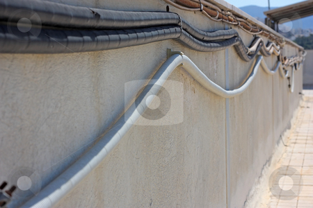 Outside Electrical Cabling stock photo, Protected electrical cables along a roof wall (focus on the first curve of the lower cable) by Georgios Alexandris