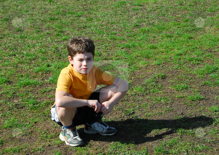 Little boy upset stock photo, Little boy sitting upset on a soccer field after losing a game by Elena Elisseeva