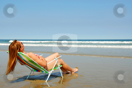 Woman relaxing on beach stock photo, Young woman relaxing in a beach chair on the ocean shore by Elena Elisseeva