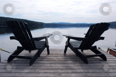 Lake chairs stock photo, Two wooden adirondack chairs on a boat dock on a beautiful lake in the evening by Elena Elisseeva