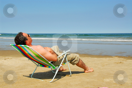 Man relaxing on beach stock photo, Man relaxing in a beach chair on the ocean shore by Elena Elisseeva