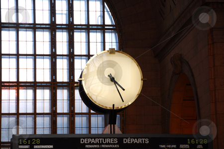Clock train station stock photo, Big clock inside a train station on top of the time table by Elena Elisseeva