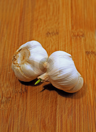 Garlic bulb stock photo, Two garlic bulbs on wooden cutting board by Elena Elisseeva