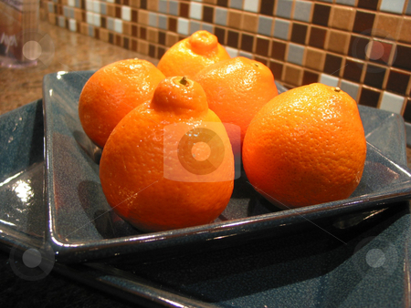 Tangerines in a bowl stock photo, Bright orange tangerines in a blue bowl on kitchen counter by Elena Elisseeva