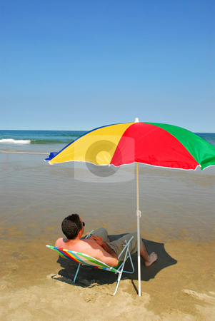 Man relax beach stock photo, Man relaxing in a beach chair on the ocean shore by Elena Elisseeva