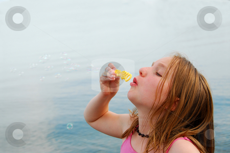 Girl blowing bubbles stock photo, Young girl blowing soap bubbles by Elena Elisseeva