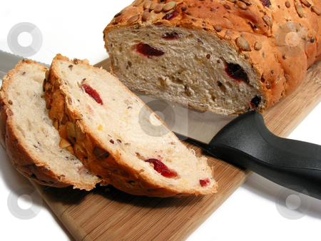 Bread and knife stock photo, Artisan pumkin seed and cranberry bread on a cutting board with a bread knife, white background by Elena Elisseeva