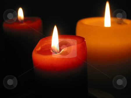 Three burning candles stock photo, Three candles burning in the dark, focus on the front candle by Elena Elisseeva