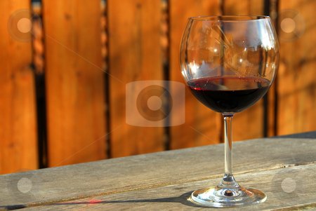 Glass of red wine stock photo, Glass of red wine on old rustic table, horisontal by Elena Elisseeva