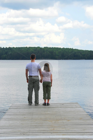 Father child lake stock photo, Father and child standing on a wooden pier on a lake holding hands by Elena Elisseeva