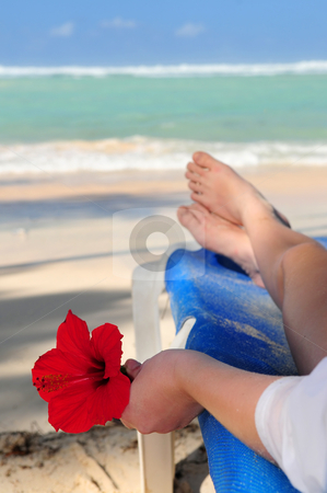 Beach relaxation stock photo, Young woman relaxing on a tropical beach holding a red flower by Elena Elisseeva