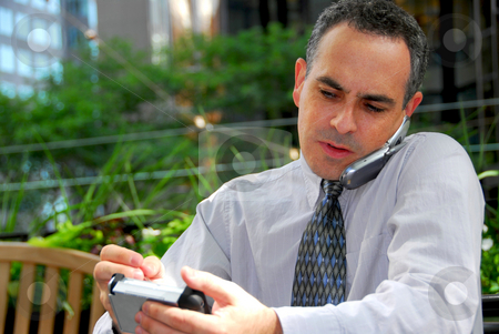 Busy businessman stock photo, Portrait of a busy businessman in the city using pda and cell phone by Elena Elisseeva