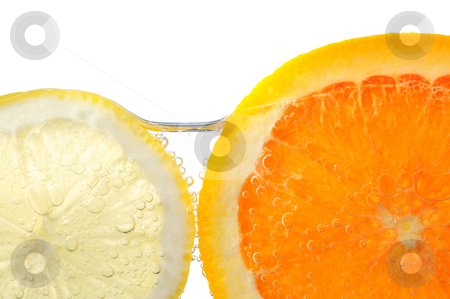 Orange and lemon slices in water stock photo, Orange and lemon slices in water with air bubbles on white background by Elena Elisseeva