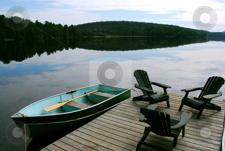 Lake chairs stock photo, Three wooden adirondack chairs on a boat dock on a beautiful lake in the evening by Elena Elisseeva