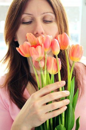 Woman with flowers stock photo, Mature woman smelling bouquet of flowers by Elena Elisseeva