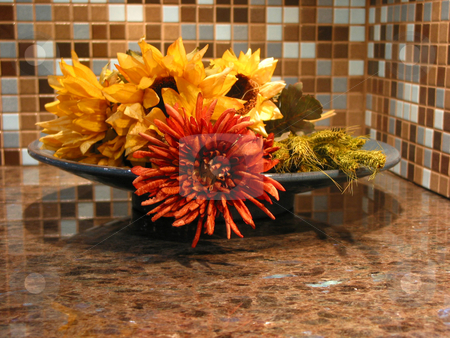 Ktchen decoration stock photo, Artificial flowers in a bowl on granite countertop in a modern kitchen by Elena Elisseeva