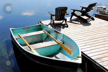 Lake chairs stock photo, Two wooden adirondack chairs on a boat dock on a beautiful still lake with sky reflection by Elena Elisseeva