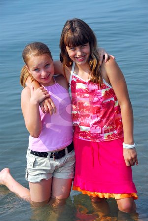 Two preteen girls stock photo, Portrait of two preteen girls standing in water by Elena Elisseeva