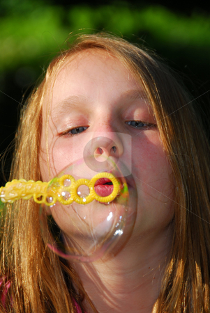 Young girl soap bubbles stock photo, Young girl blowing soap bubbles - one big bubble by Elena Elisseeva