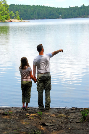 Father daughter lake stock photo, Father and daughter standing on the lake shore and looking at calm water, father pointing out something in the distance by Elena Elisseeva