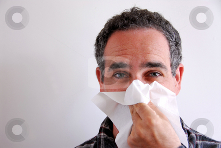 Sick man blowing nose stock photo, Man with a flu blowing his nose by Elena Elisseeva