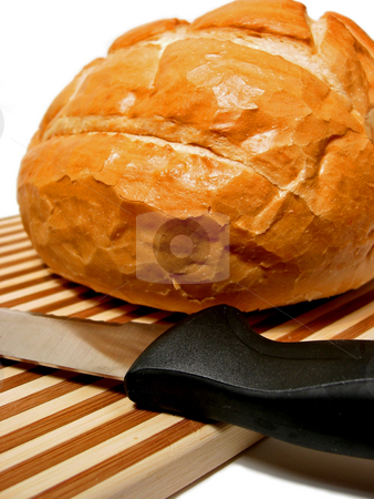 Bread stock photo, Fresh loaf of sourdough bread on a cutting board with bread knife by Elena Elisseeva