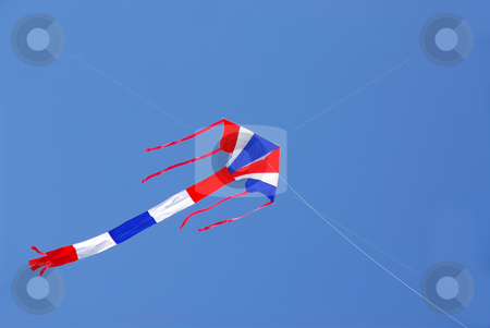 Flying kite stock photo, Kite with american flag colors flying in clear blue sky by Elena Elisseeva