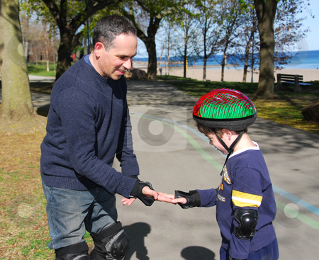 Father and son rollerblading stock photo, Father and son rollerblading together by Elena Elisseeva